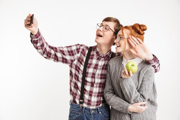 Coppia sorridente di nerd della scuola che prendono selfie