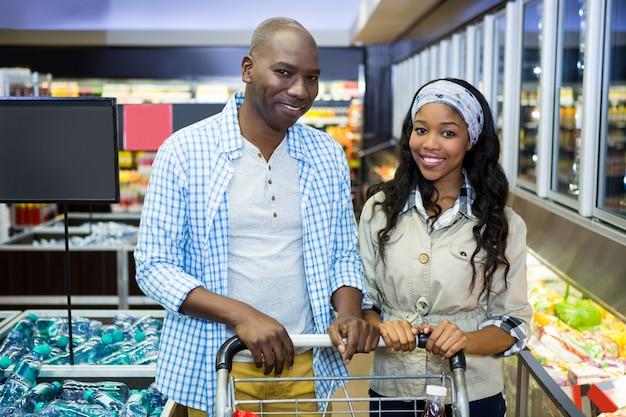 Acquisto sorridente delle coppie nella sezione della drogheria al supermercato