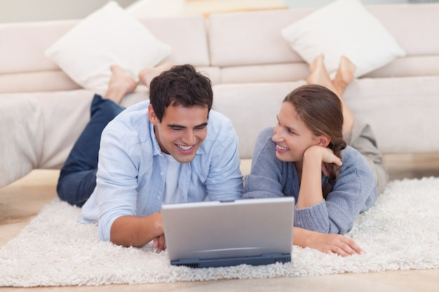 Coppie sorridenti che praticano il surfing su internet