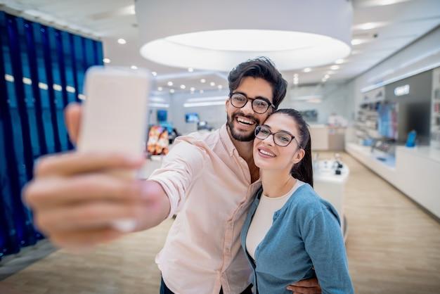 Coppie sorridenti che prendono selfie mentre levandosi in piedi nel negozio di tecnologia. concetto di tecnologie contemporanee.