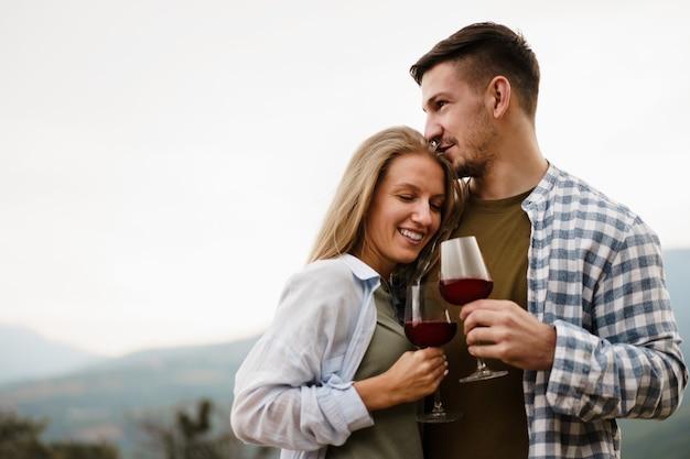 Coppia sorridente che tosta bicchieri di vino all'aperto in montagna, ritratto ravvicinato