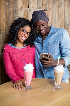 Coppie sorridenti facendo uso del telefono cellulare contro la parete di legno