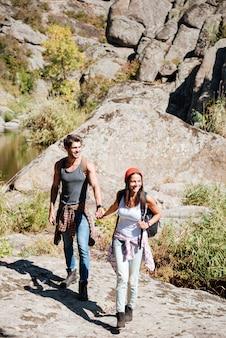 Coppie sorridenti che camminano insieme con gli zaini sopra le montagne