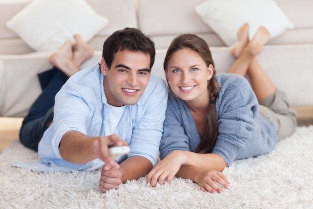 Coppie sorridenti che guardano tv mentre trovandosi su un tappeto