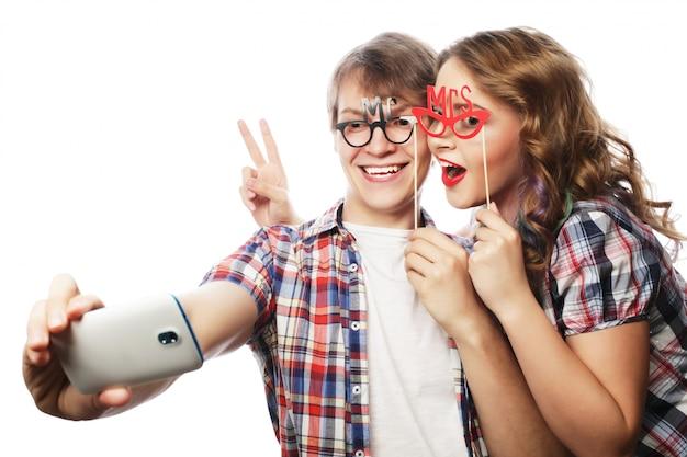 Coppia sorridente con smartphone, selfie e divertimento.