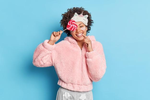 Sorridente giovane donna dai capelli ricci copre gli occhi con sorrisi di lecca-lecca ampiamente vestita in pigiama sleepmask isolato sopra la parete blu. la bella femmina si prepara per dormire utilizza prodotti per la cura della pelle