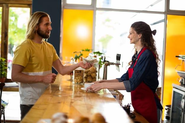 Cliente sorridente che paga fattura in contanti al contatore
