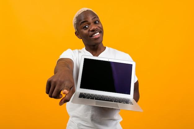 Americano sveglio sorridente in maglietta bianca che mostra l'esposizione del computer portatile con il modello e che indica dito in avanti sul fondo arancio dello studio