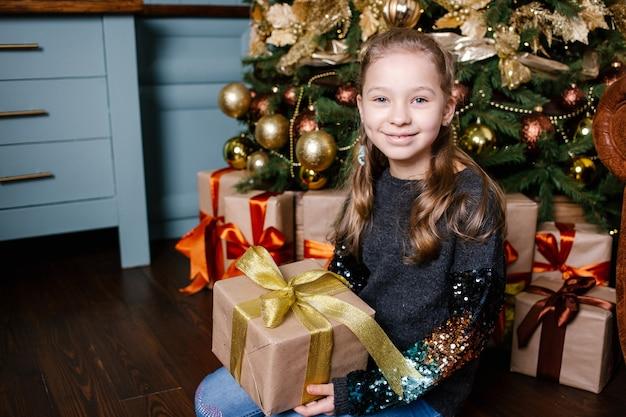 Sorridente ragazza carina bambino che tiene il regalo di natale in mano dall'albero di natale.