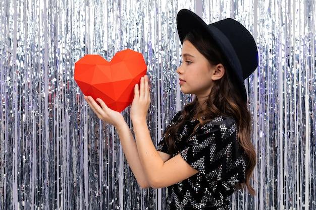 La ragazza sveglia sorridente in un vestito e un cappello festivi tiene una forma del cuore rosso su un lucido con canutiglia.