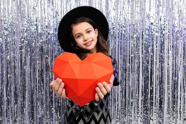 La ragazza sveglia sorridente in vestito e cappello festivi tiene un cuore di carta rosso su un lucido con canutiglia. san valentino