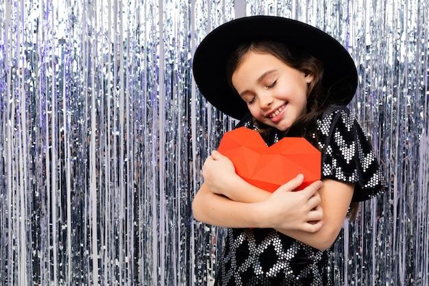 La ragazza sveglia sorridente in un vestito festivo e un cappello abbraccia un cuore di carta rosso su un lucido con canutiglia.