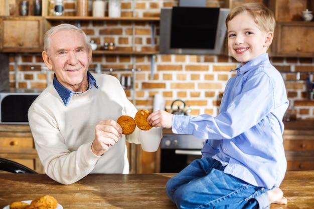 Ragazzino sveglio sorridente seduto sul tavolo mentre mangia i biscotti con suo nonno