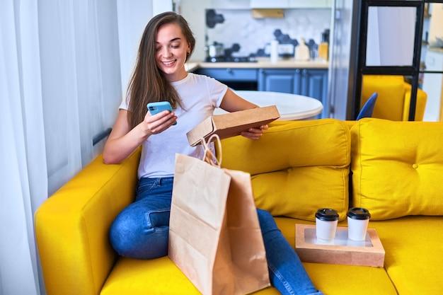 Sorridente carino soddisfatto felice casual adulto gioiosa giovane donna millenaria acquirente ha ricevuto sacchetti di cartone con cibo e bevande da asporto a casa. concetto di servizio di consegna veloce