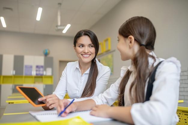 Insegnante sveglio sorridente che spiega con il tablet alla studentessa attenta che si siede accanto al banco di scuola