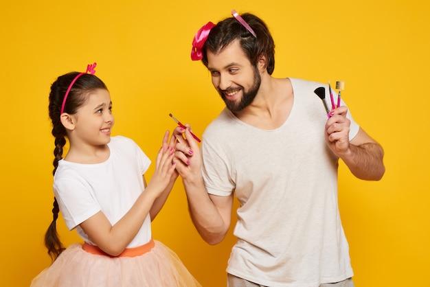 Il papà sorridente pulisce il fronte delle figlie con una spazzola.