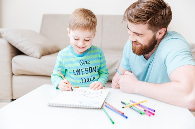 Papà sorridente e figlio piccolo che disegnano con pennarelli colorati a casa