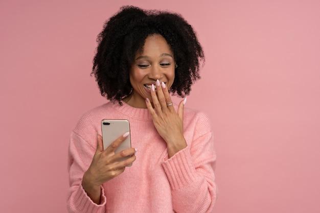 Sorridente donna millenaria dalla pelle scura guardando il telefono cellulare in stato di shock