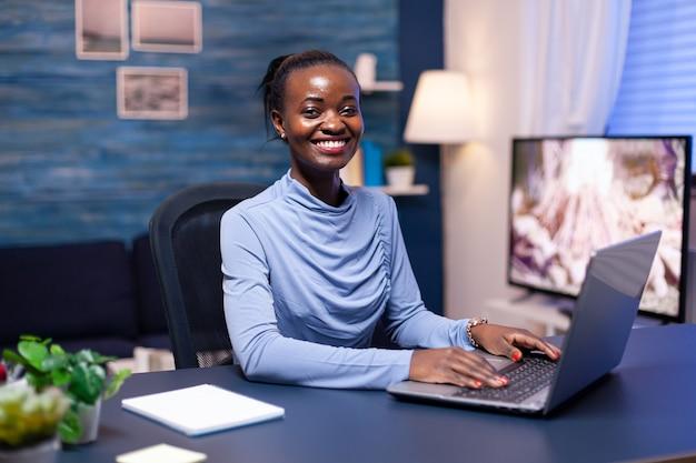 Donna dalla pelle scura sorridente che sorride alla macchina fotografica che si siede allo scrittorio che lavora a tarda notte dall'ufficio domestico. libero professionista nero che lavora con una conferenza virtuale online in chat di gruppo in remoto.