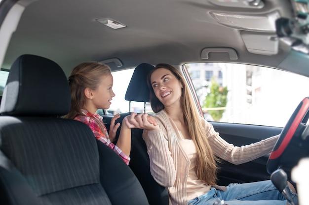 Figlia sorridente che tiene la mano di sua madre, alla guida dell'auto