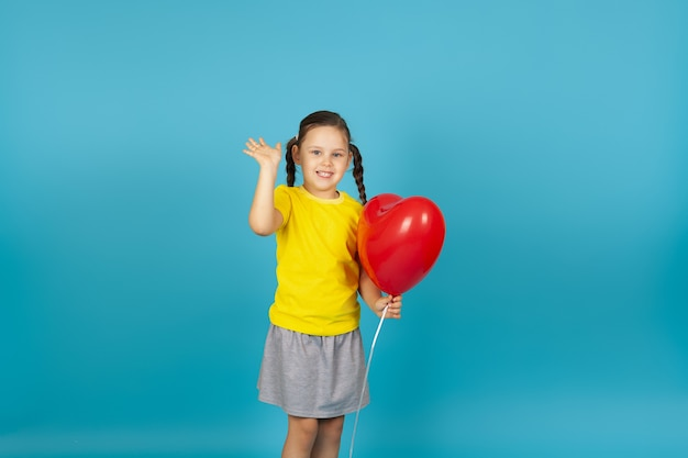 Sorridente ragazza felice tiene un palloncino rosso a forma di cuore e le onde mano