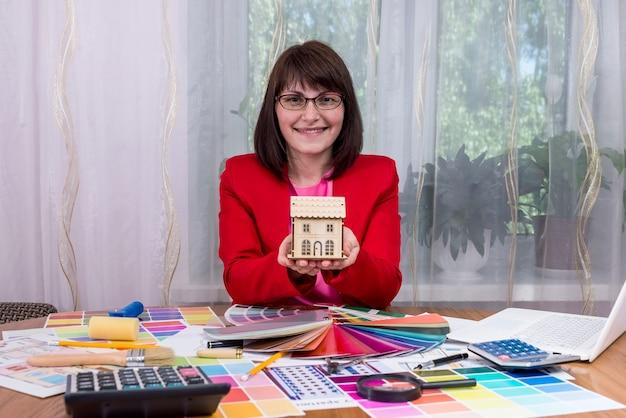 Designer sorridente che mostra il progetto della casa in ufficio