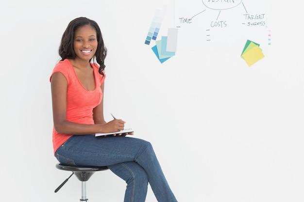 Progettista sorridente che si siede e che scrive davanti alla lavagna