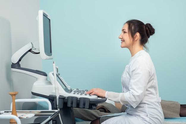 Il dottore sorridente fa l'ecografia alla donna in ospedale