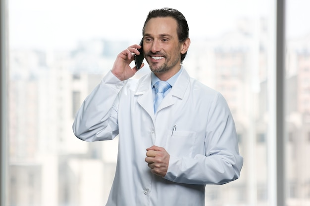 Il medico sorridente sta parlando al telefono. finestre luminose sullo sfondo.