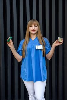 Medico sorridente che offre pillole in blister. donna che indossa divisa medica e guanti protettivi