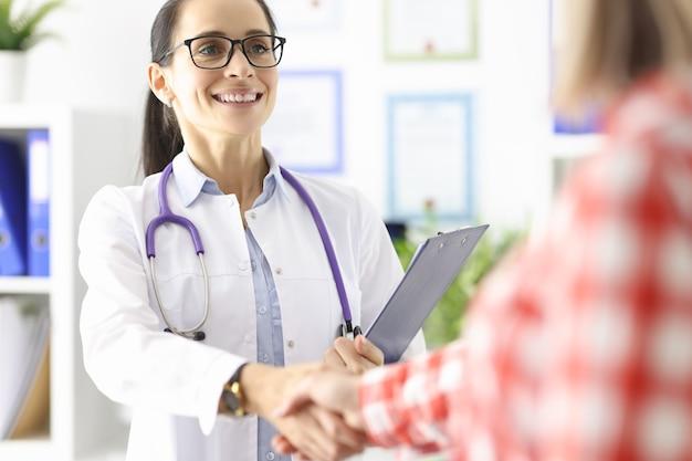 Il medico sorridente stringe la mano al concetto di assicurazione medica del paziente
