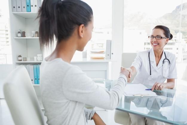 Medico sorridente che agita la mano dei pazienti