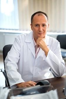 Medico sorridente che si siede allo scrittorio nell'ufficio. man in scrub in posa. avvicinamento.