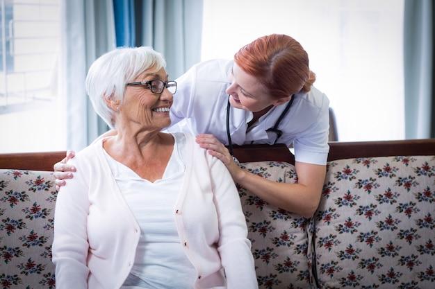 Medico sorridente che parla con donna senior felice