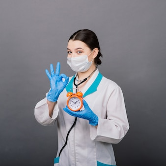 Sorridente donna medico in maschera che punta sull'orologio, tempo per il vaccino, concetto medico