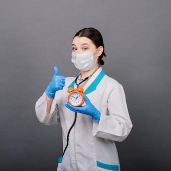 Sorridente donna medico in maschera che punta sull'orologio, è ora di vaccinare