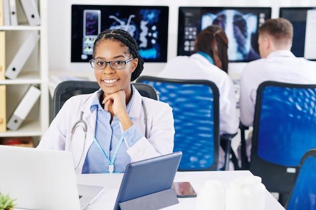 Medico sorridente che lavora al computer portatile