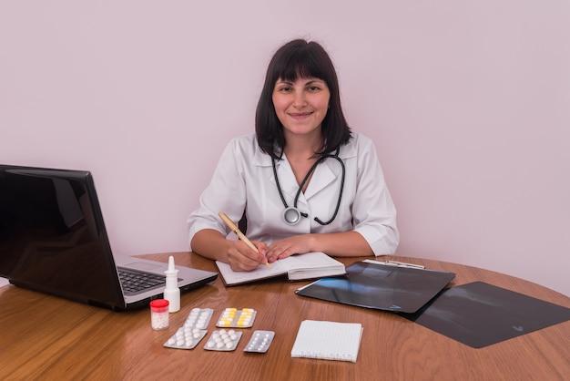 Medico sorridente sul posto di lavoro con i raggi x del paziente