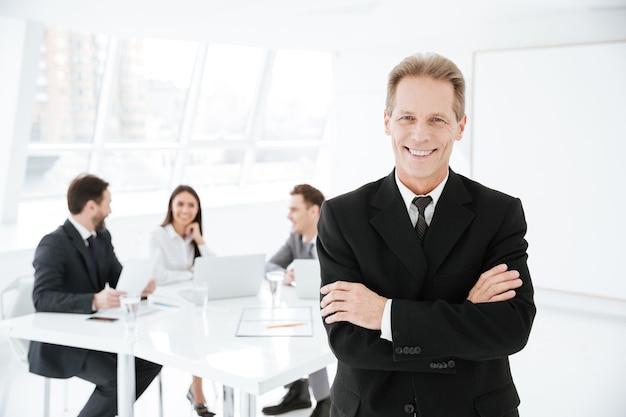 Uomo d'affari anziano sorridente in piedi con le braccia incrociate in ufficio con i colleghi