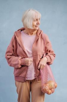 Sorridente donna anziana in un'accogliente felpa con cappuccio che trasporta un sacco di cotone con generi alimentari contro il muro blu.