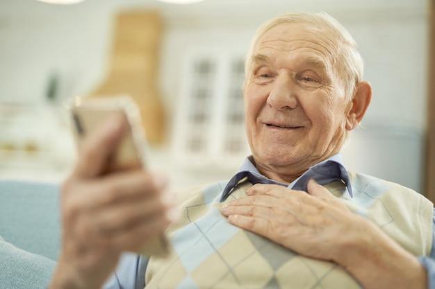 Uomo anziano sorridente che tiene un telefono cellulare a casa