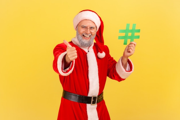 Uomo anziano sorridente con la barba grigia che indossa il costume di babbo natale che tiene l'hashtag verde in mano e mostra il pollice in su, sito web consigliato. colpo dello studio dell'interno isolato su priorità bassa gialla.