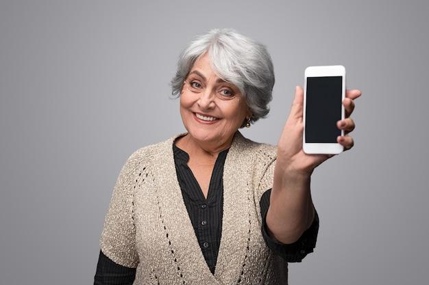 Sorridente donna anziana che mostra smartphone
