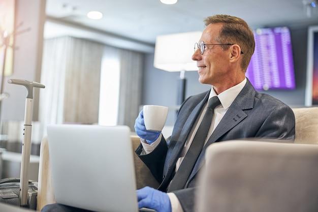 Sorridente maschio elegante che indossa guanti in lattice mentre beve caffè con il taccuino prima del volo durante la pandemia