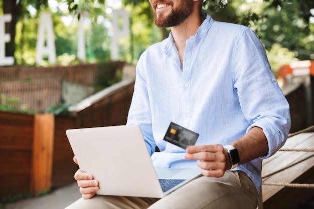 Sorridente emotivo giovane uomo barbuto utilizzando il computer portatile
