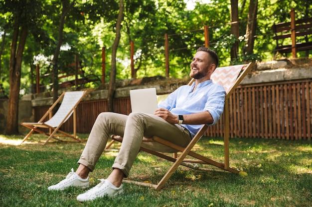 Sorridente emotivo giovane uomo barbuto