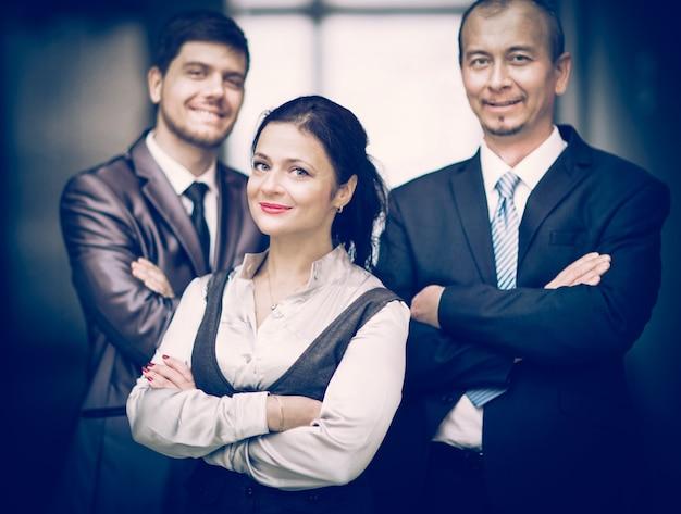 Dipendenti sorridenti in piedi uno dietro l'altro in ufficio