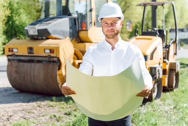 Ingegnere sorridente con casco in piedi davanti all'escavatore sul cantiere stradale