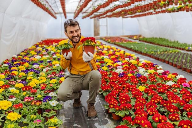 Imprenditore sorridente accovacciato in serra e offrendo fiori come regalo.