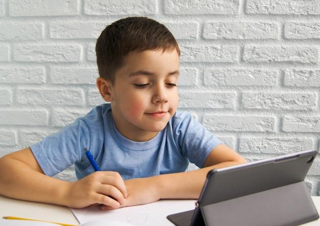 Il ragazzo bambino europeo sorridente in maglietta blu sta usando un laptop e comunica su internet a casa. istruzione domiciliare, apprendimento a distanza, istruzione online, videochiamata